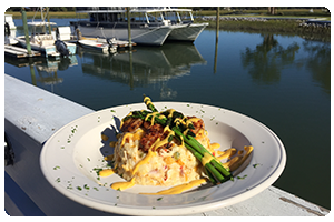 A daily Salty Dog Café special featuring shrimp and grits paired                  with fresh asparagus and a waterfront view.