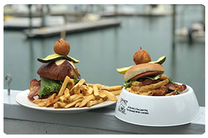 Hamburger and french fries on a plate , and a hamburger and fries in a souviner dog bowl on a Pier.