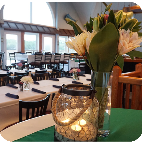 Rope and glass lantern with lit candle, clear glass vase with flowers on a green table runner. The background is tables set for a private event.