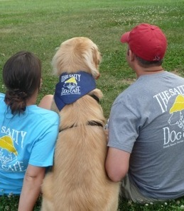 The backs of a  man and woman wearing salty dog t-shirts with a dog in a salty dog bandana